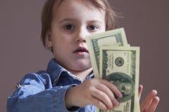 De dollarsbankbiljetten van een kindholding Ontwikkeling, zaken succes Royalty-vrije Stock Afbeeldingen