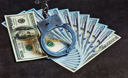 de 100 dollarsrekeningen leggen ventilator en metaalhandcuffs op hen Royalty-vrije Stock Afbeeldingen
