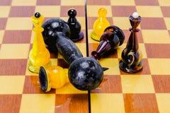 De domoor ligt op een schaakbord, op witte schaakkoning, is de zwarte dichtbij gevallen De overwinning van macht over de mening stock fotografie