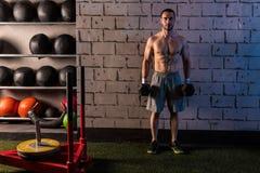 De domoren van de de holdingshexuitdraai van de gymnastiekmens met spieren Stock Fotografie