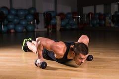 De Domoren van Doing Pushups With van de jonge Mensenatleet als deel van Bodybuilding-Opleiding Stock Afbeelding