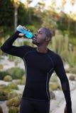De donker-gevilde gezonde mens met mooi lichaam drinkt water in openlucht na training Royalty-vrije Stock Afbeeldingen