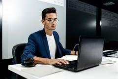 De donker-haired jonge architect kleedde zich in het matrozenwerk aangaande laptop in het bureau stock afbeeldingen