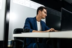De donker-haired jonge architect kleedde zich in het matrozenwerk aangaande laptop in het bureau royalty-vrije stock foto's
