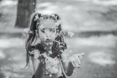 De donker-haired jonge vrouw blaast cottonwood pluis Royalty-vrije Stock Foto