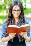 De donker-haired jonge vrouw leest rood Stock Foto