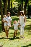 De donker-haired mooie vrouw draagt de witte modieuze kleren en de hoedengangen met knappe vader en kinderen in stock foto's