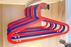 De donkerblauwe en rode hangers wegen in een geval Stock Fotografie