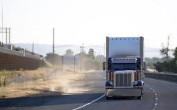 De donkerblauwe grote semi vrachtwagen van de installatie klassieke bonnet met lichte tellers die lading in droge bestelwagen sem royalty-vrije stock foto
