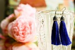 De donkerblauwe oorringenleeswijzers sluiten omhoog mening met kleurrijk boeket op vage achtergrond Vrouwelijk concept accesserie stock afbeeldingen