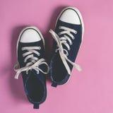 De donkerblauwe Tennisschoenen op roze pastelkleurvlakte als achtergrond lagen Stock Foto's
