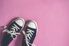 De donkerblauwe Tennisschoenen op roze pastelkleurvlakte als achtergrond leggen exemplaarruimte Royalty-vrije Stock Fotografie