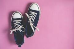 De donkerblauwe Tennisschoenen op roze pastelkleurvlakte als achtergrond leggen exemplaarruimte Royalty-vrije Stock Afbeeldingen