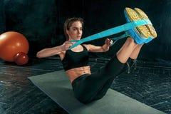 De donkerbruine atletische vrouw die met rubberband uitoefenen Stock Afbeelding
