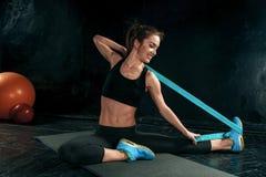 De donkerbruine atletische vrouw die met rubberband uitoefenen Royalty-vrije Stock Afbeelding