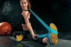 De donkerbruine atletische vrouw die met rubberband uitoefenen Stock Foto