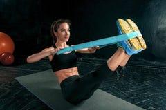 De donkerbruine atletische vrouw die met rubberband uitoefenen Stock Afbeeldingen