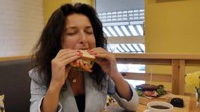 De donkerbruine bedrijfsdame in een matroos, eet een verse weelderige sandwich in een comfortabele koffie met gele muren stock footage