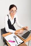 De donkerbruine bedrijfsdamewerken aangaande computer Stock Foto