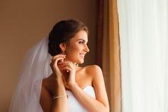De donkerbruine bruid glimlacht terwijl het aanpassen van haar oorringen Royalty-vrije Stock Fotografie
