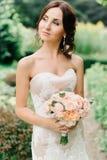 De donkerbruine bruid kijkt weg houdend perzikboeket in haar wapens Stock Foto's