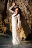De donkerbruine bruid leunt op grote klip in water Stock Fotografie