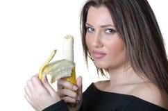 De donkerbruine dame pelt een banaan Stock Foto