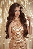 De donkerbruine dame van de manierglamour in gouden glanzende lovertjeskleding over Stock Fotografie