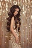 De donkerbruine dame van de manierglamour in gouden glanzende lovertjeskleding over Stock Foto's