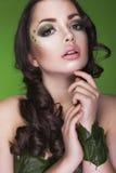 De donkerbruine dryadevrouw met creatief maakt omhoog en parels op haar gezicht, krullend die haar en kostuum van bladeren op gro Stock Fotografie
