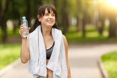 De donkerbruine fles van de meisjesholding water na sport in park Royalty-vrije Stock Foto's