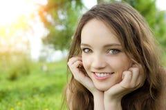 De donkerbruine glimlach van het tienermeisje op weide Royalty-vrije Stock Afbeelding