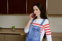 De donkerbruine huisvrouw in blauwe overall drinkt sap van een glas is Royalty-vrije Stock Afbeelding