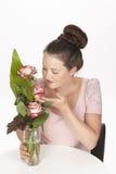 De donkerbruine jonge vrouw geniet van een boeket van rozen Royalty-vrije Stock Afbeeldingen
