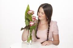 De donkerbruine jonge vrouw geniet van een boeket van rozen Royalty-vrije Stock Foto