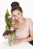 De donkerbruine jonge vrouw geniet van een boeket van rozen Royalty-vrije Stock Fotografie