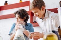 De donkerbruine jongen die van Nice de chemische fles houden Stock Afbeelding