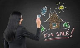De donkerbruine makelaar in onroerend goed trekt een nieuw kleurrijk huis op het zwarte bord Royalty-vrije Stock Foto's