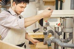 De donkerbruine mens bored houten raad op boringsmachine Stock Foto's