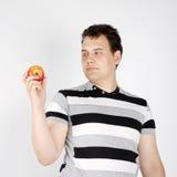 De donkerbruine mens houdt appel Stock Afbeeldingen