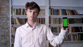 De donkerbruine mens toont het groene scherm van smartphone, lettend op bij camera, communicatie concept, bibliotheek op achtergr stock video