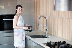 De donkerbruine pot van de vrouwenholding in keuken Stock Foto