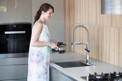 De donkerbruine pot van de vrouwenholding over keukengootsteen Royalty-vrije Stock Fotografie