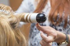 De donkerbruine rode kunstenaar die van de haarkapper krullend kapsel maken aan B Stock Foto's