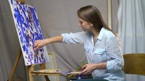 De donkerbruine schilder concentreert vervenolieverven op canvas met een spatel die in ruimte sitiing stock videobeelden