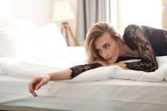 De donkerbruine sexy vrouw ligt op binnen gekleed bed in lingerie Royalty-vrije Stock Fotografie