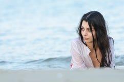 De donkerbruine slanke bikini van de de slijtagebodem van de lichaamsdame en nat wit overhemd Stock Afbeeldingen