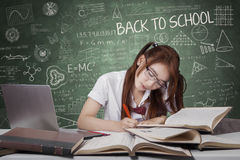 De donkerbruine student leert op de lijst in klasse Stock Afbeelding