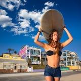 De donkerbruine surfplank van de het meisjesholding van de surfertiener in een strand Royalty-vrije Stock Foto