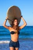 De donkerbruine surfplank van de het meisjesholding van de surfertiener in een strand Royalty-vrije Stock Afbeeldingen